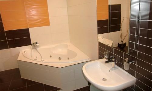 Modernes Badezimmer weiß gefliest, aufgelockert mit farbigen, orangen und schwarzen Fliesen, Eckbadewanne mit Massagefunktion