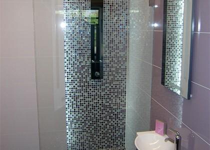 Modernes Badezimmer gefliest in lila violett mit Mosaikfliesen im Duschbereich